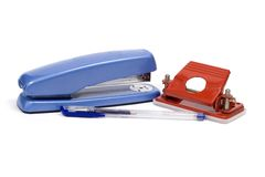 Office supplies. A stapler, hole punch and pen on a white background Stock Photos