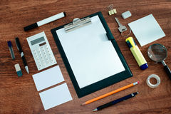 Office Supplies Arranged Around Clipboard on Desk. High Angle View of Office or School Supplies Arranged Neatly Around Clipboard with Blank Page on Wooden Desk Royalty Free Stock Image