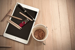 Office supplies, empty coffee cup, and tablet Stock Image
