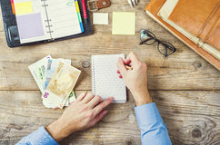 Office supplies, gadgets and money on wooden table Royalty Free Stock Photo