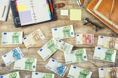 Office supplies, gadgets and money on wooden table Stock Images