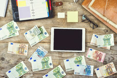 Office supplies, gadgets and money on wooden table Royalty Free Stock Images