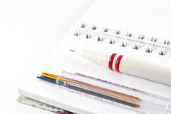 Office supplies - Mechanical pencil with pencil leads on white notebook. Office supplies on white background Royalty Free Stock Photos