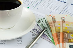 Office supplies with money and cup of coffee Stock Image
