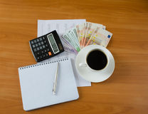 Office supplies with money and cup of coffee Royalty Free Stock Photography