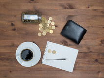 Office supplies with money jar and coins cup of coffee Stock Photo