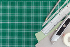 Office supplies over green cutting mat background. top view. Royalty Free Stock Image