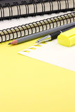 Office supplies, pencils, marker notebooks lying on yellow desk Stock Images