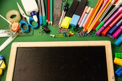 Office supplies for school and a drawing board on a green backgr stock image