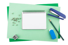 Office supplies on textured colored paper imitating a frame. Office supplies on textured colored paper: a notebook, sheets of textured paper, a pencil, an eraser Stock Photo