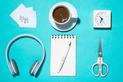 Office supplies. Top view on opened notebook, pen, headphone, cl Stock Photography