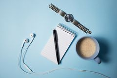 Office supplies. Top view on opened notebook, pen, headphone, laptop and cup of coffee on blue. Office supplies. Top view on opened notebook, pen, headphone royalty free stock image