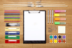 Office supplies on wooden flooring, clipboard with empty paper. Colorful office supplies on wooden flooring, with clipboard, color pencils, markers Stock Photos