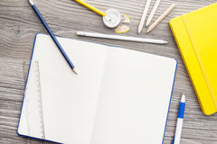 Office supply collection. Sharpener, pencils, ball pen, notebooks and ruler - on brown wooden table Stock Images