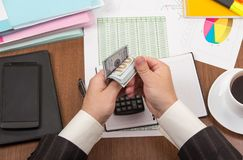 Office table with accessories, men`s hands count money Stock Photography