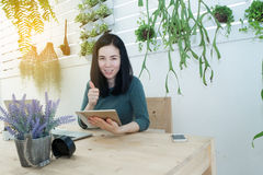 Office table with Asian woman in smiling face and hand holding s Royalty Free Stock Photos