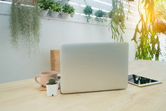 Office table with back of screen laptop, coffee cup, tablet and Royalty Free Stock Image