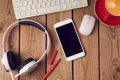 Office table background with smartphone, headphones and computer keyboard. Business workplace or workspace concept. Stock Photos