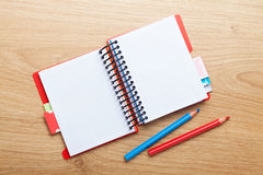 Office table with blank notepad and colorful pencils Royalty Free Stock Images