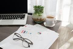 Office table with business summary report , white coffee cup and. Wood office table with business summary report , white coffee cup and blank screen on laptop at Stock Images