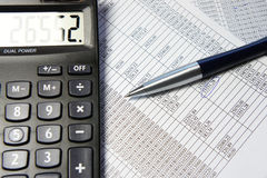 Office table with calculator, pen and accounting document Royalty Free Stock Image