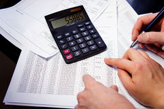 Office table with calculator, pen and accounting document. Calculator, pen and accounting document with a lot of numbers and woman hands Stock Photos