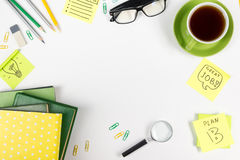 Office table desk with green supplies, blank note pad, cup, pen, glasses, crumpled paper, magnifying glass, flower on Stock Photo