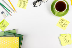 Office table desk with green supplies, blank note pad, cup, pen, glasses, crumpled paper, magnifying glass, flower on Royalty Free Stock Images