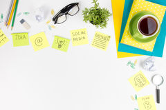 Office table desk with green supplies, blank note pad, cup, pen, glasses, crumpled paper, magnifying glass, flower on Stock Images