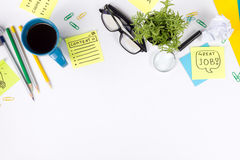Office table desk with green supplies, blank note pad, cup, pen, glasses, crumpled paper, magnifying glass, flower on Stock Photos