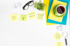 Office table desk with green supplies, blank note pad, cup, pen, glasses, crumpled paper, magnifying glass, flower on Stock Photography