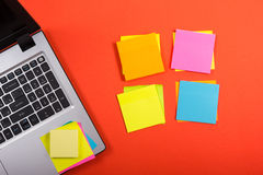 Office table desk with set of colorful supplies, laptop and reminder on red background. Top view. Copy space for text Royalty Free Stock Image