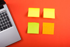 Office table desk with set of colorful supplies, laptop and reminder sticky note on red background. Top view. Copy space Royalty Free Stock Photo