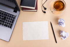 Office table desk with set of colorful supplies, white blank note pad, cup, pen, pc, crumpled paper, flower on beige Royalty Free Stock Photos