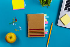 Office table desk with set of colorful supplies, white blank note pad, cup, pen, pc, crumpled paper, flower on blue Royalty Free Stock Photography