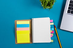 Office table desk with set of colorful supplies, white blank note pad, cup, pen, pc, crumpled paper, flower on blue Royalty Free Stock Image