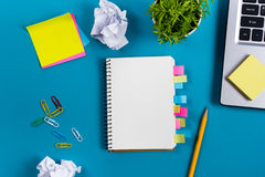 Office table desk with set of colorful supplies, white blank note pad, cup, pen, pc, crumpled paper, flower on blue Stock Images