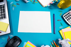 Office table desk with set of colorful supplies, white blank note pad, cup, pen, pc, crumpled paper, flower on blue Royalty Free Stock Images