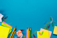 Office table desk with set of colorful supplies, white blank note pad, cup, pen, pc, crumpled paper, flower on blue. Background. Top view and copy space for Royalty Free Stock Image