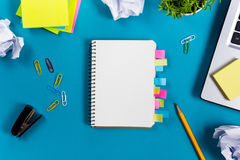 Office table desk with set of colorful supplies, white blank note pad, cup, pen, pc, crumpled paper, flower on blue. Background. Top view and copy space for stock images