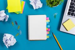 Office table desk with set of colorful supplies, white blank note pad, cup, pen, pc, crumpled paper, flower on blue Stock Photography