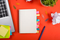 Office table desk with set of colorful supplies, white blank note pad, cup, pen, pc, crumpled paper, flower on red Stock Images