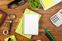 Office table desk with set of colorful supplies, white blank note pad, cup, pen, pc, crumpled paper, flower on wooden Stock Image