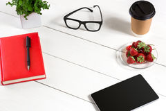 Office table desk with set of supplies, red notepad, cup, pen, tablet, glasses, flower on white background. Top view Stock Image