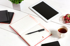 Office table desk with set of supplies, white blank notepad, cup, pen, tablet, flower on white background. Top view Stock Photo