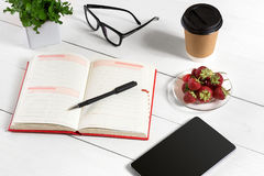 Office table desk with set of supplies, white blank notepad, cup, pen, tablet, glasses, flower on white background. Top Stock Photos