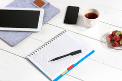 Office table desk with set of supplies, white blank notepad, cup, pen, tablet on white background. Top view. And copy space for text Stock Photos