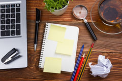 Office table desk with supplies, white blank note pad, cup, pen, pc, crumpled paper, flower on wooden background. Top Stock Image