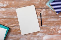 Office table desk with supplies, white blank note pad, cup, pen, pc, crumpled paper, flower on wooden background. Top Stock Photography