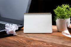Office table desk with supplies, white blank note pad, cup, pen, pc, crumpled paper, flower on wooden background. Top Royalty Free Stock Photos